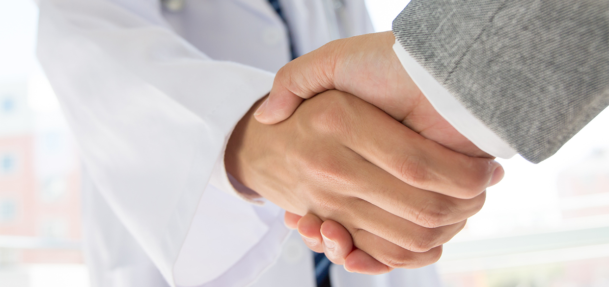 Doctor and businessman shaking hands